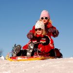 Kids Snow Sledding Down Hill